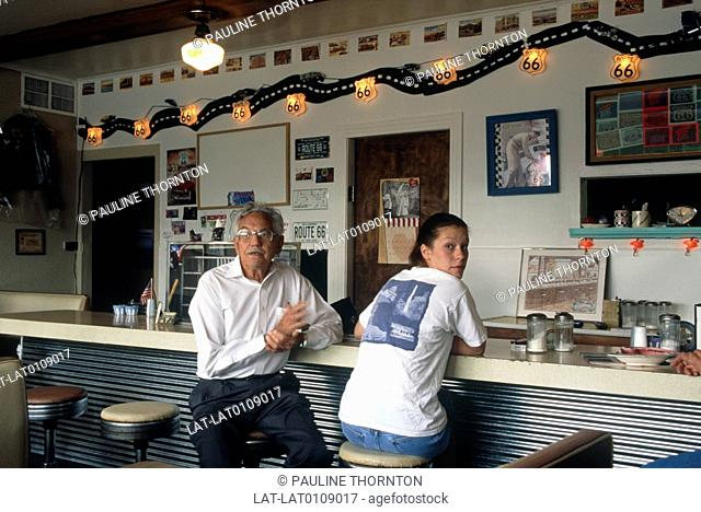 Diamond Bart's cafe. Exterior. Duck egg blue wall. Signs. Route 66. Two people