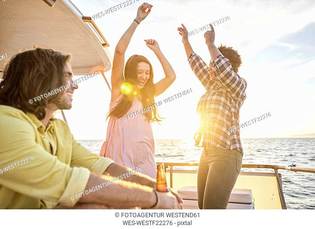 Happy friends having a party on a boat trip