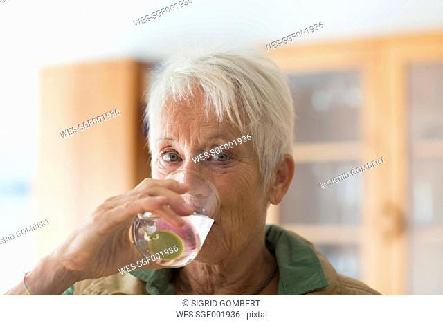 Portrait of white haired senior woman drinking glass of water