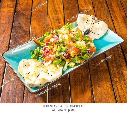 Grilled fish fillet with a vegetable salad,