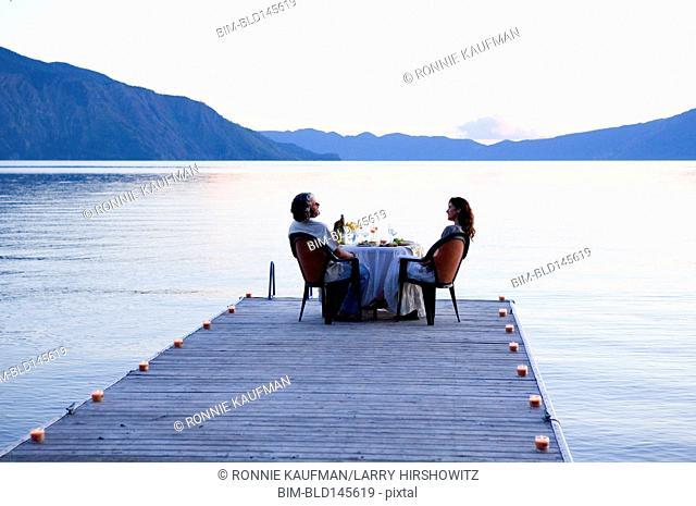 Caucasian couple having dinner on pier at lake