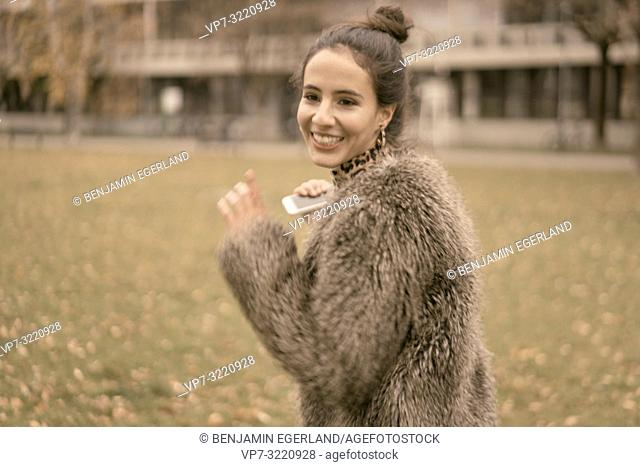 fashionable vital woman running outdoors in park, autumn season, wearing coat, happiness, candid lively emotion, unposed walking in city, Munich, Germany