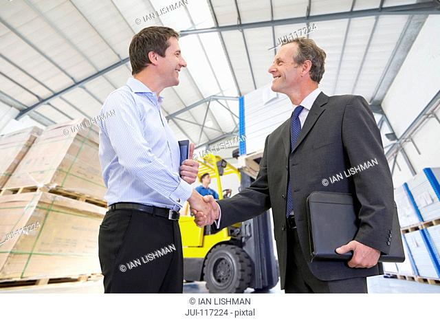 Businessman Meeting In Solar Panel Manufacturing Warehouse