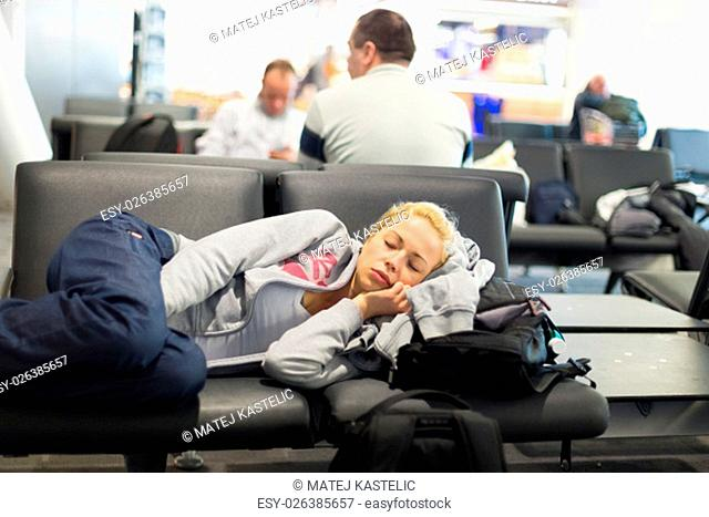 Tired female traveler sleeping on the airpot departure gates bench with all her luggage by her side. Tireing travel concept