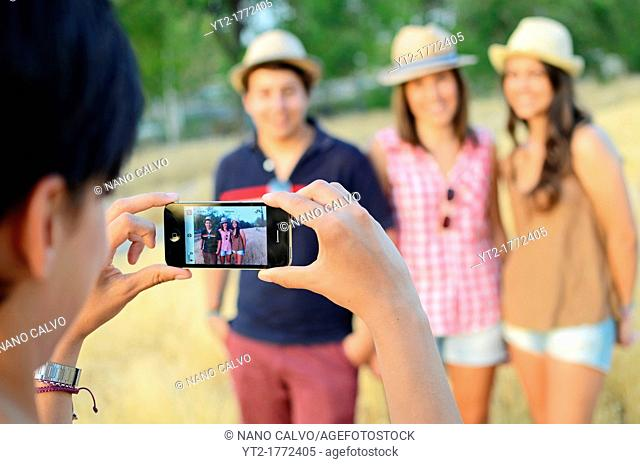 Young woman takes a photo of two girls and a boy, with mobile phone