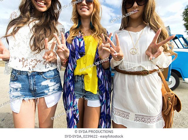 smiling young hippie women showing peace sign