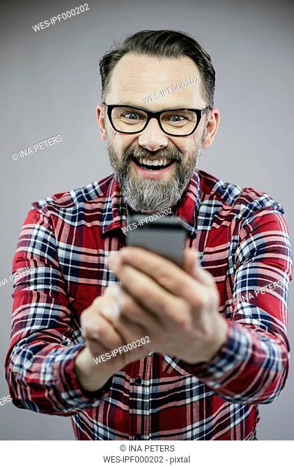 Portrait of excited man looking at smartphone