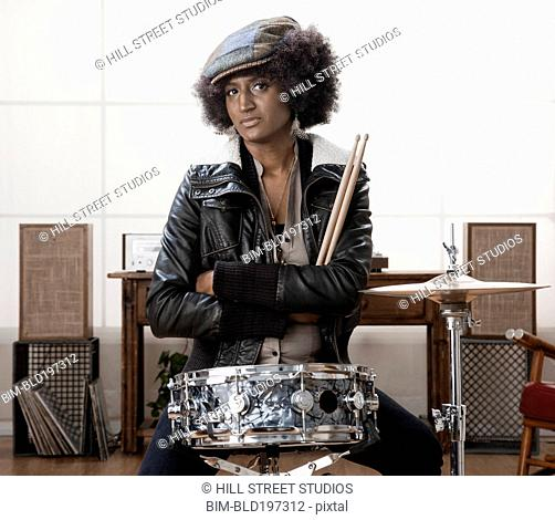 Serious mixed race woman sitting with drums