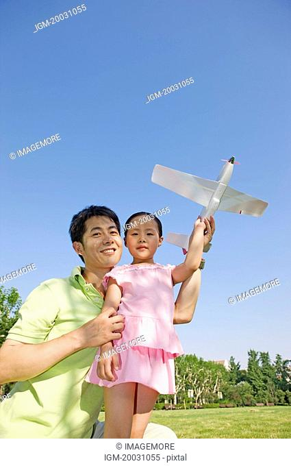 Family, father and daughter playing toy airplane in a park