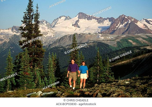Young couple hikes in alpine meadow atop Whistler, British Columbia, Canada