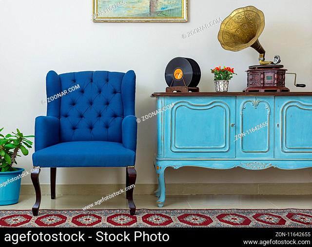 Vintage interior of retro blue armchair, vintage wooden light blue sideboard, old phonograph (gramophone), vinyl records on background of beige wall