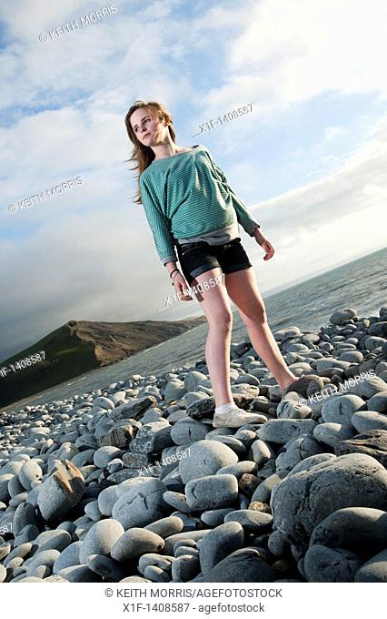 A 12 year old girl standy on a rocky beach, wales UK
