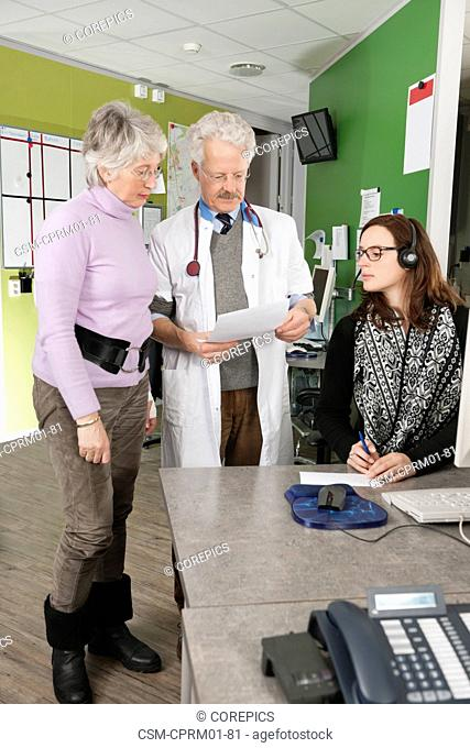 Doctor holding a note, reading it to two of his assistants