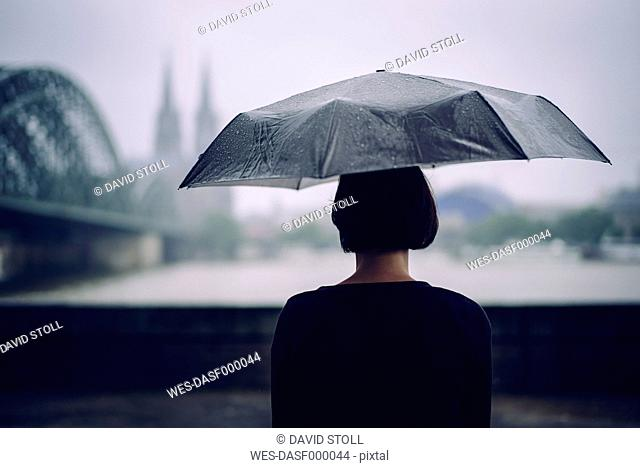 Germany, Cologne, back view of woman with umbrella on a rainy day