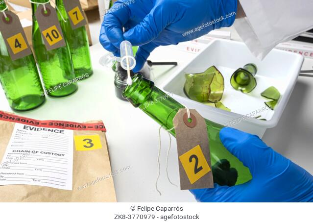 Police expert gets blood sample from a green glass bottle in Criminalistic Lab, conceptual image