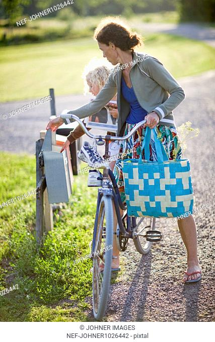 Sweden, mother and daughter (4-5) on bike checking mail