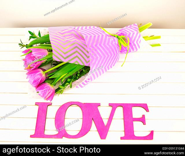 bouquet of purple tulips on white table, wooden letters love