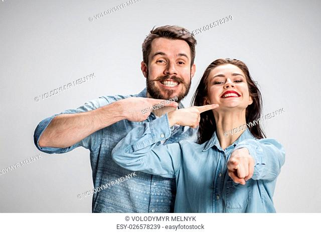 The business man and woman on a gray background pointing fingers at wide smile girl