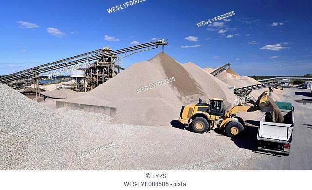 Wheel loader loading gravel on truck