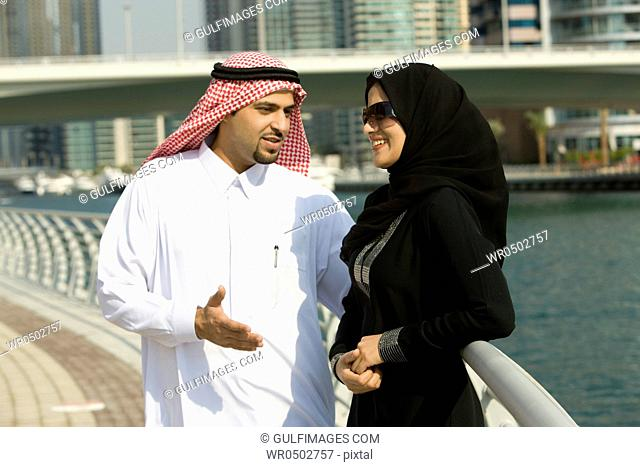 Arab couple standing by the railing in Dubai Marina, UAE
