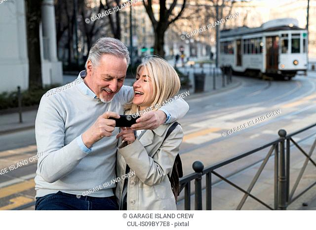 Senior couple using smartphone on sidewalk in city