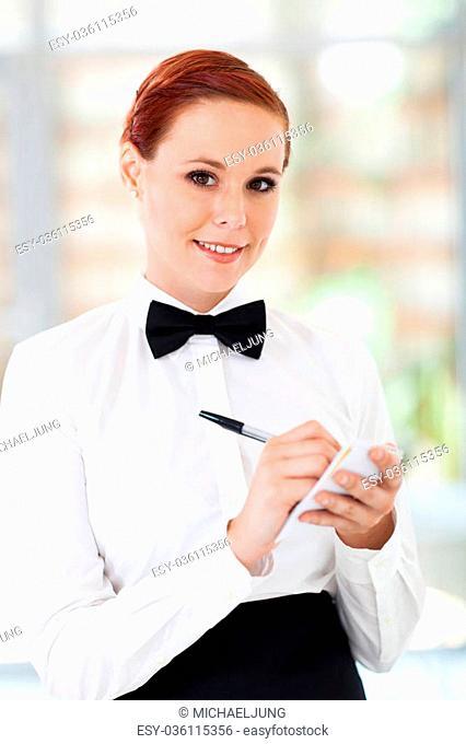 pretty waitress taking orders in restaurant