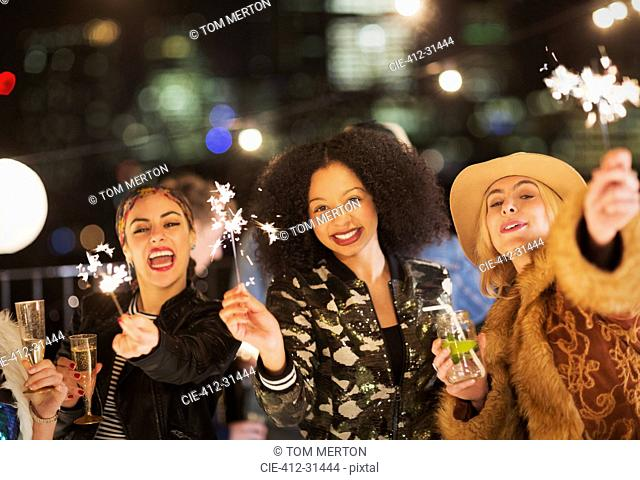 Portrait enthusiastic young women waving sparklers at party