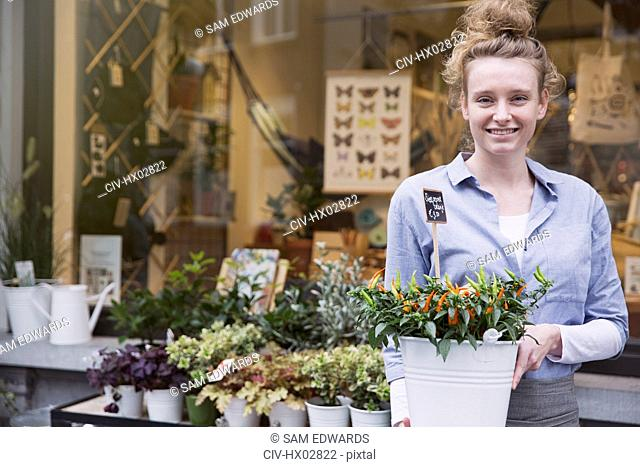 Portrait smiling female florist with potted plant at storefront