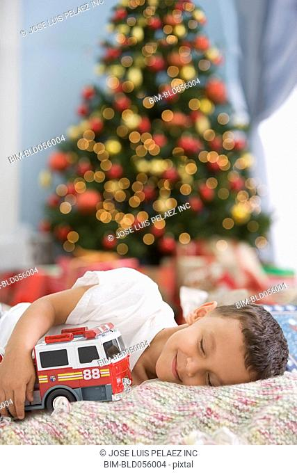 Hispanic boy sleeping in front of Christmas tree