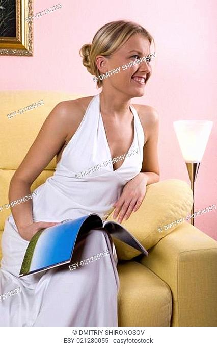 Smiling woman with the fashion magazine on her knee