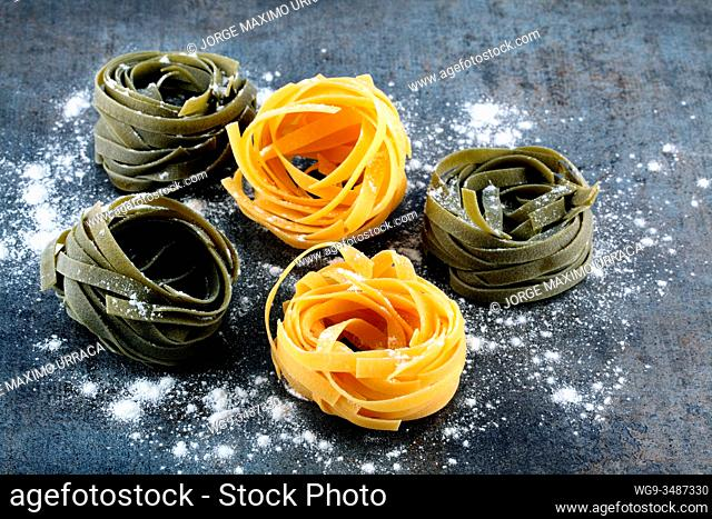 Tagliatelle pasta for cooking on artistic background