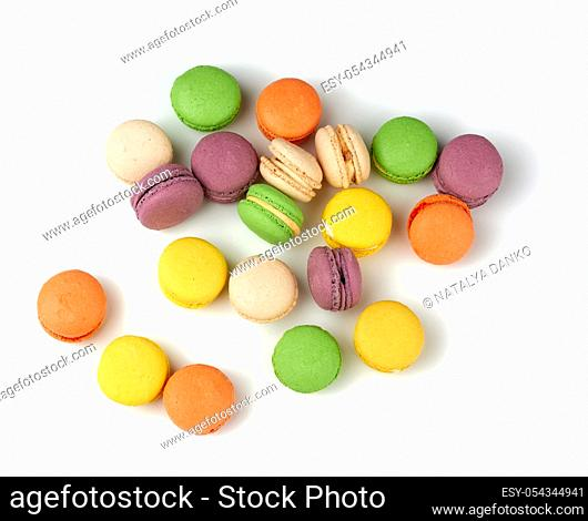 round baked multi-colored almond flour cakes macarons, dessert isolated on a white background, top view