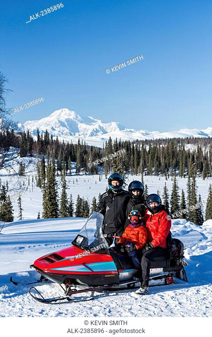 Family posing next to their snowmachine while riding in the Petersville area, Mt. McKinley in the background, Southcentral Alaska, Winter