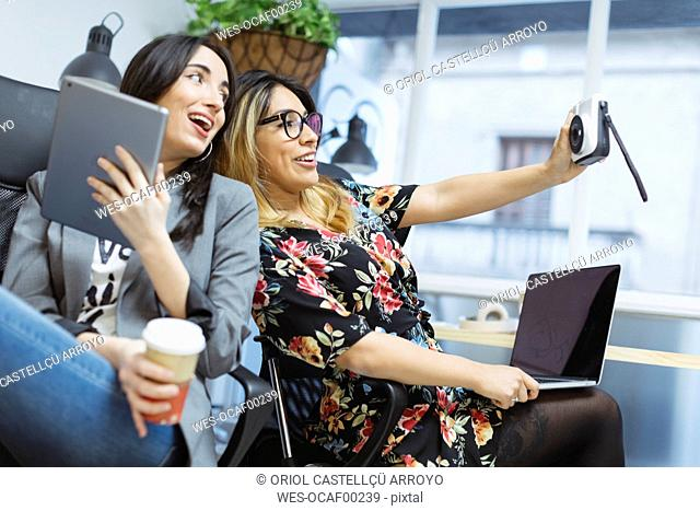 Two happy young women in the office taking a selfie