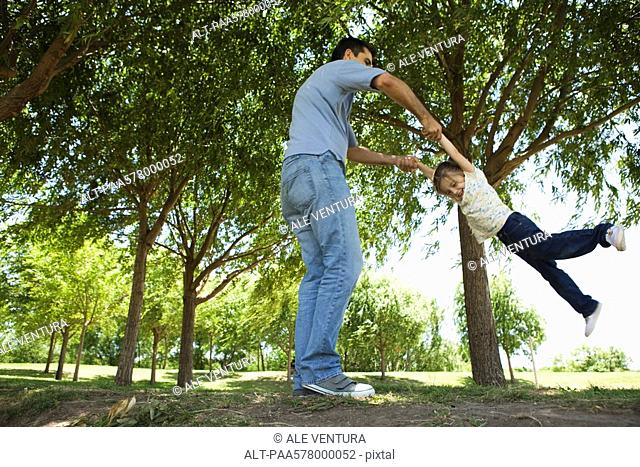 Father swinging his young daughter by her arms