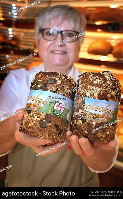 """12 June 2020, Bavaria, Hammelburg: Inge Scheller holds a barley and spelt bread baked with Franconian wine in her bakery (to dpa: """"""""Sausage"""