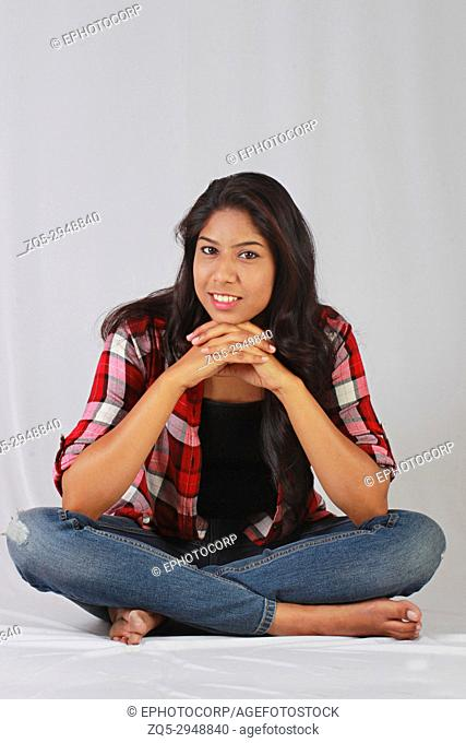 Young Indian girl in casual attire sitting cross legged