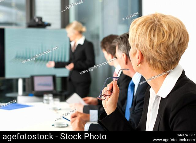 Business - presentation within a team, a female colleague is standing on the flipchart