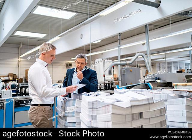 Two businessmen discussing paper in a factory