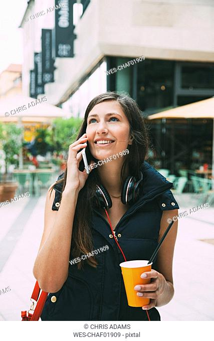 Portrait of smiling young woman on cell phone with takeaway drink in the city