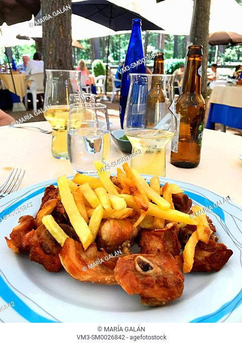 Fried pork meat with chips in a terrace restaurant