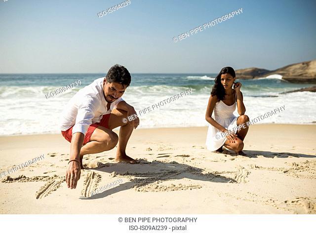 Couple writing in sand on Arpoador beach, Rio De Janeiro, Brazil