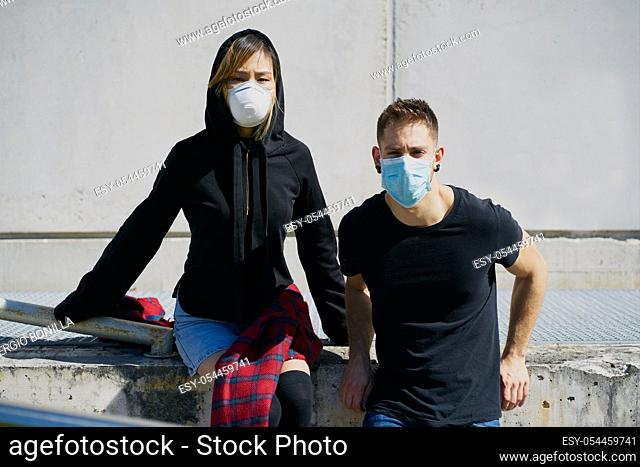 Caucasian male and Asian female wearing medical masks as a defense against a virus. The concept of Coronavirus