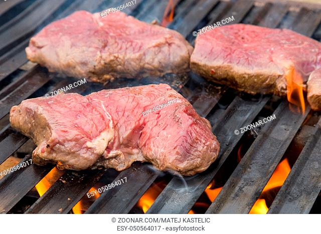 Raw beef steaks on the grill with flames