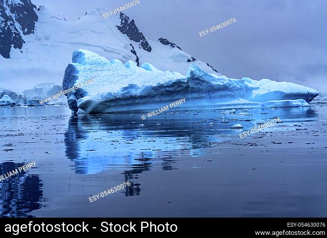 Floating Blue Iceberg Reflection Snow Mountains Paradise Bay Skintorp Cove Antarctica. Glacier ice blue because air squeezed out of snow
