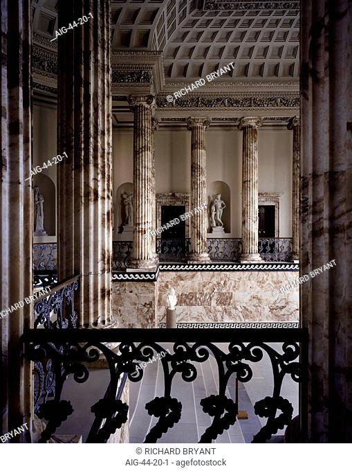 Holkham Hall, Norfolk, England. The Marble Hall, which is Derbyshire alabaster. Decoration on the ceiling and pillars. Ironwork balustrade