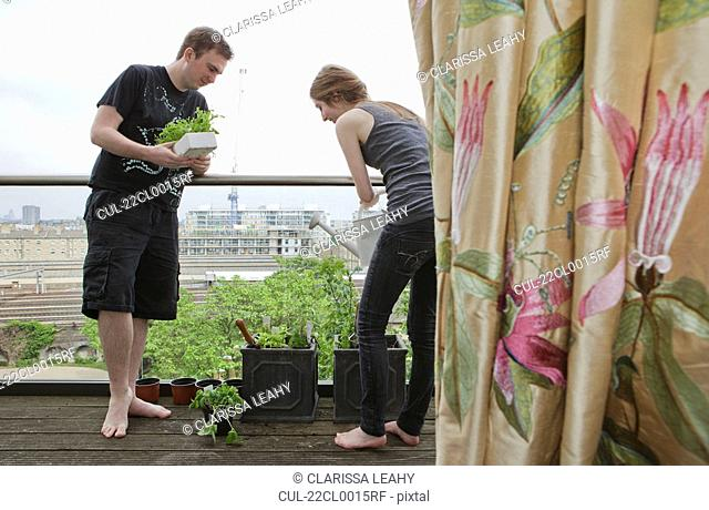 Man and woman planting up flower pots