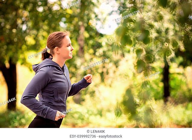 Beautiful fit runner woman jogging in nature outdoor