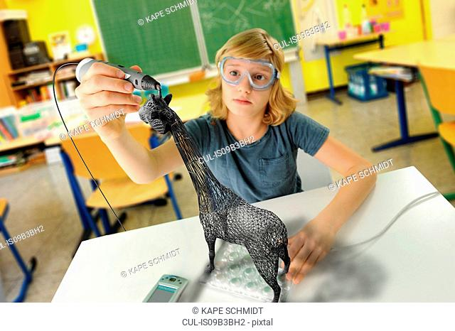 Boy with digital pen and 3D model of giraffe in classroom