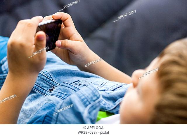 Cropped image of boy using mobile phone while lying on hammock in back yard